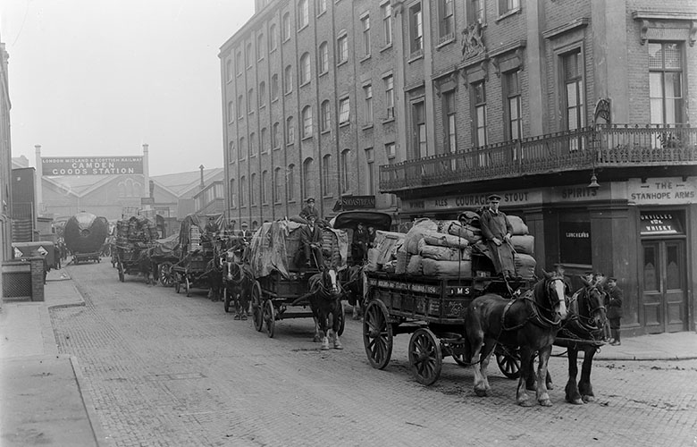 A procession of horse drawn traffic leaves the Camden Goods Depot in 1934.
